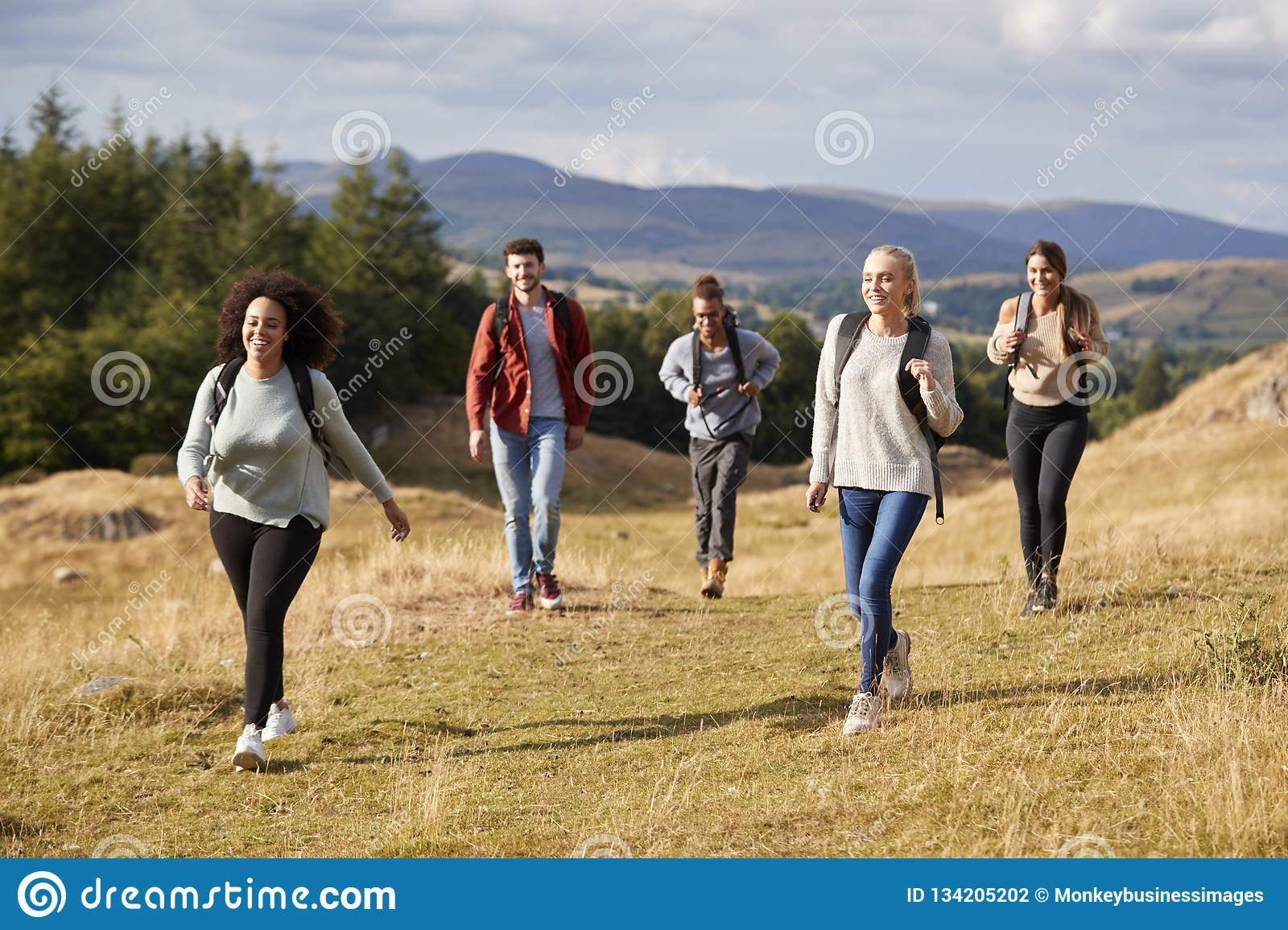 Multi ethnic group of five happy young adult friends walking on a rural path during a mountain hike, close up