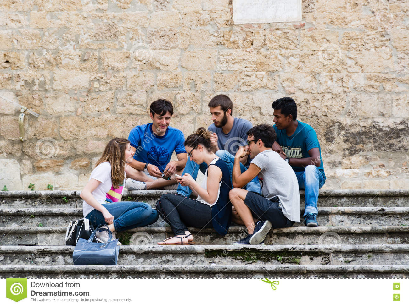 A multi-ethnic group of guys having fun chatting on the stairs o