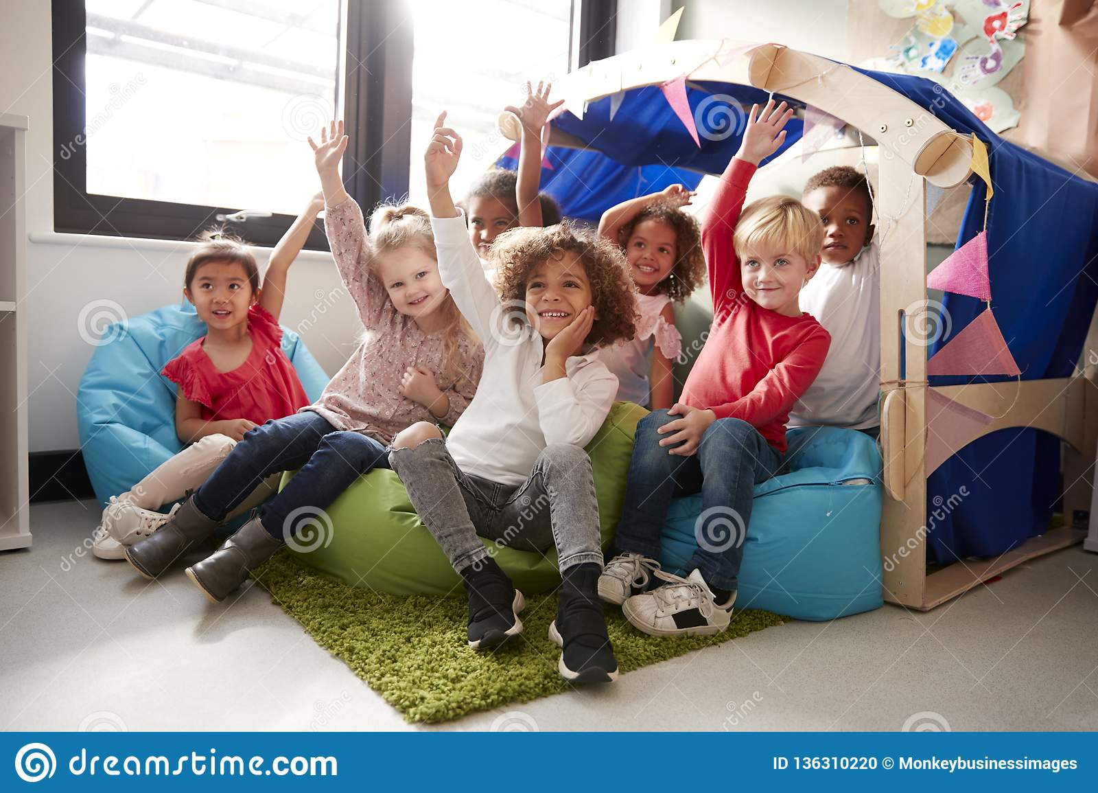 A multi-ethnic group of infant school children sitting on bean bags in a comfortable corner of the classroom, raising their hands