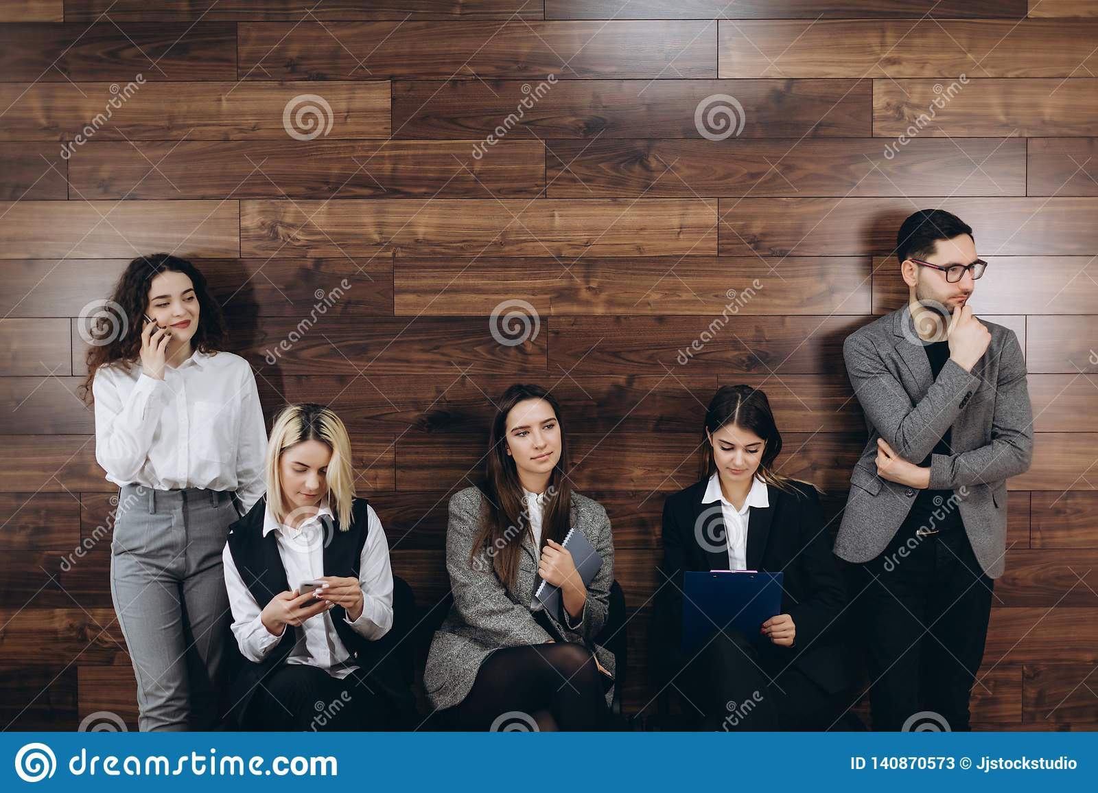 Multi-ethnic Millennial People Holding Phones And Resumes Preparing