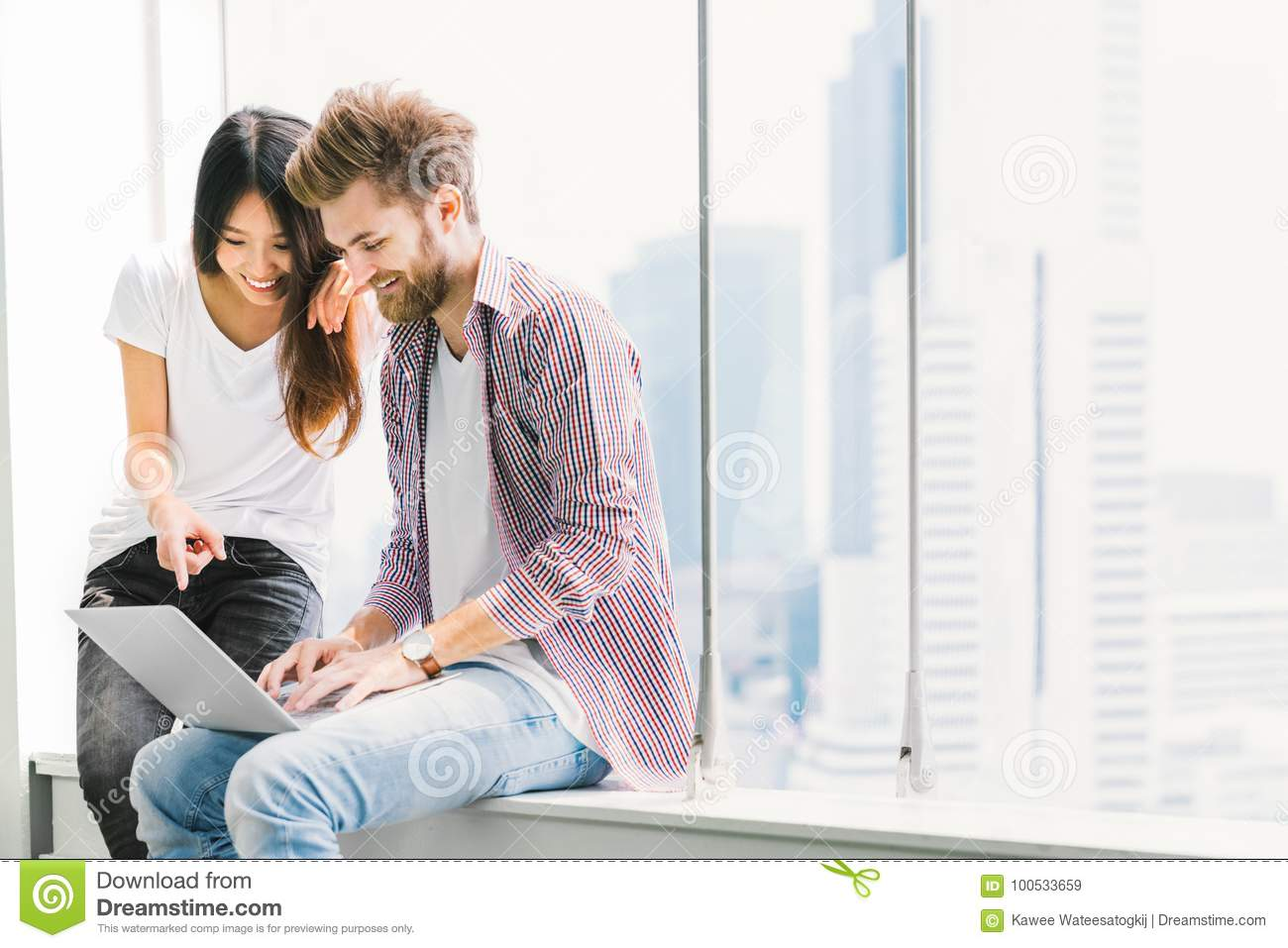 Multi-ethnic young couple or college student using notebook laptop together in campus or office. Information technology concept