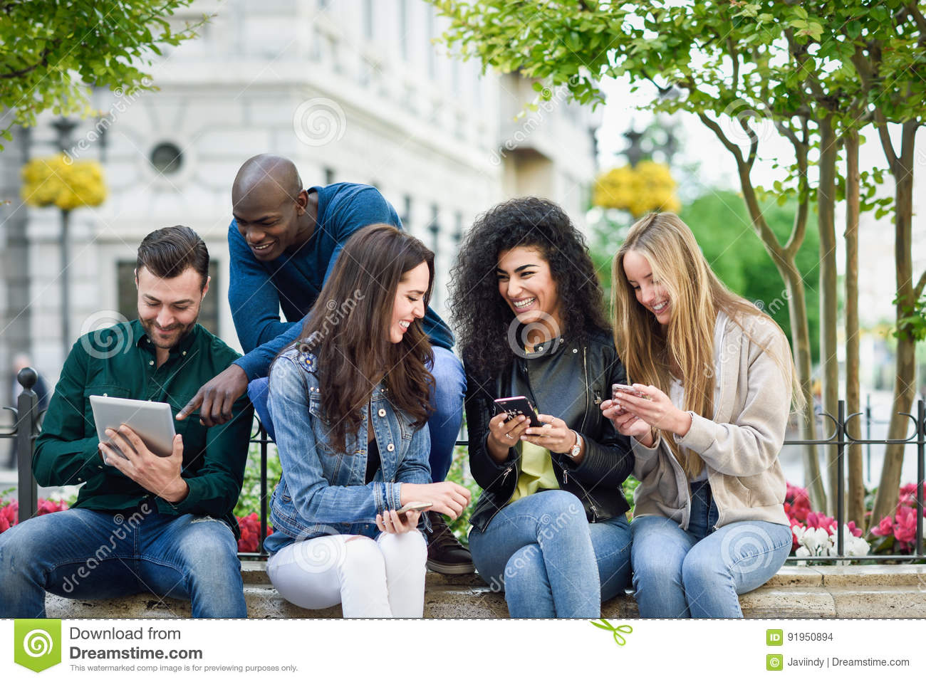 Multi-ethnic young people using smartphone and tablet computers