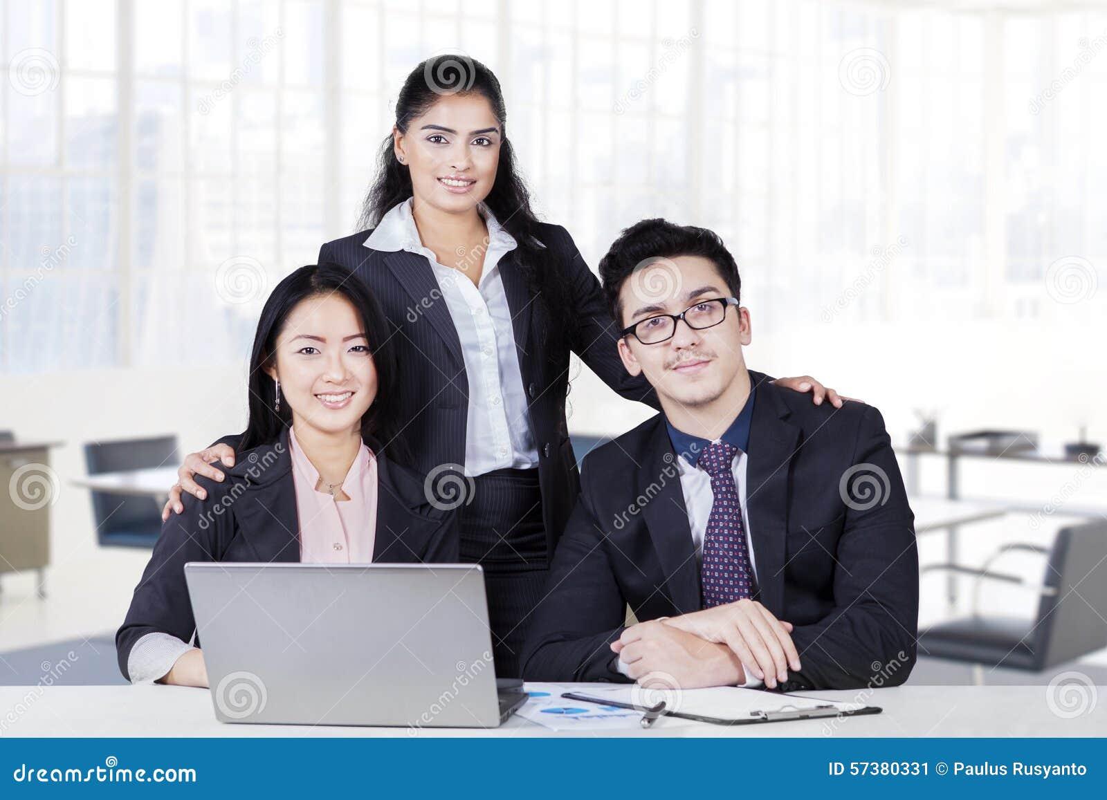Multi etnisch commercieel drie team die in bureau glimlachen