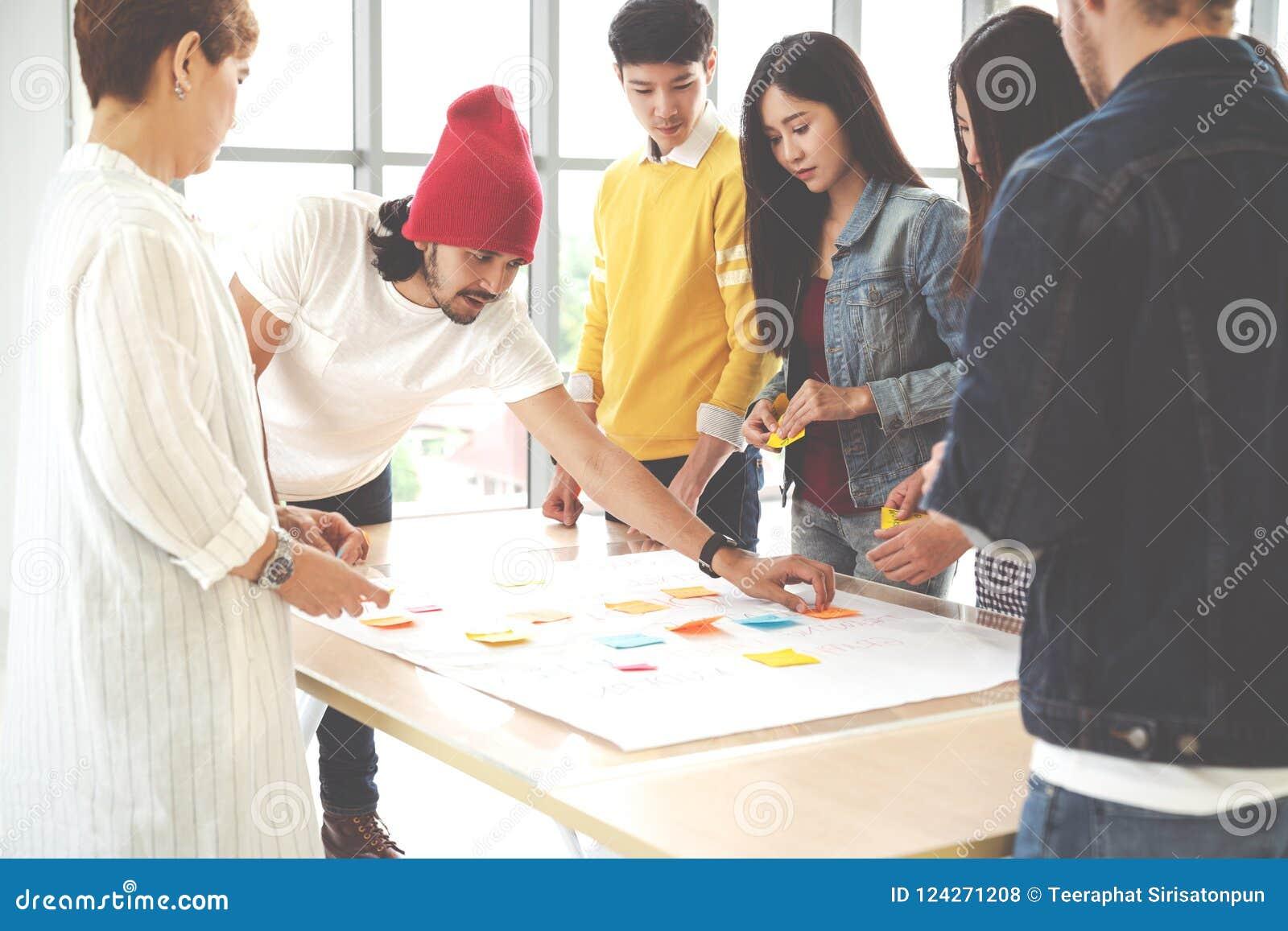 Multi-etnisch creatief team die, en brainstorming op lijst in werkplaats samenkomen samenwerken De uitwisseling van ideeën van he