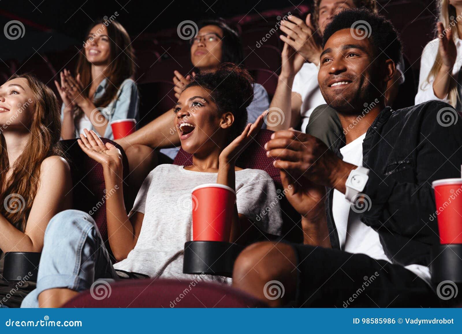 Multi-etnisch gelukkig publiek die handen slaan