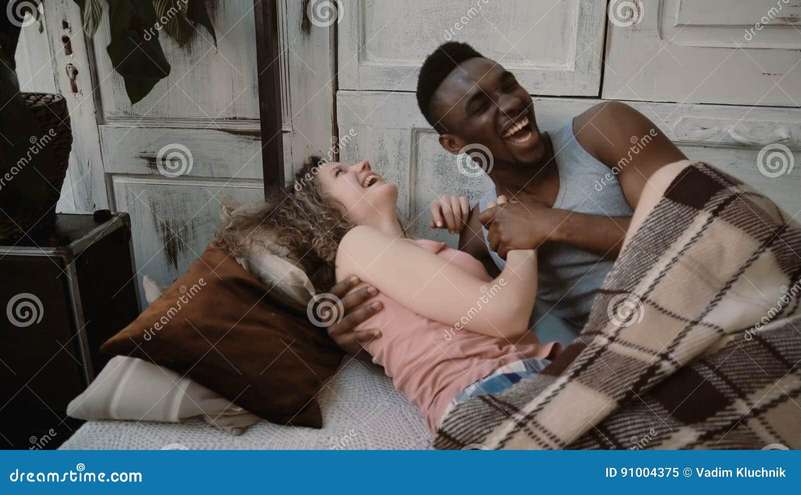 Multi-etnisch paar die op bed, La liggen die hun handen houden Het mannetje en het wijfje kijken gelukkig De man en de vrouw geni