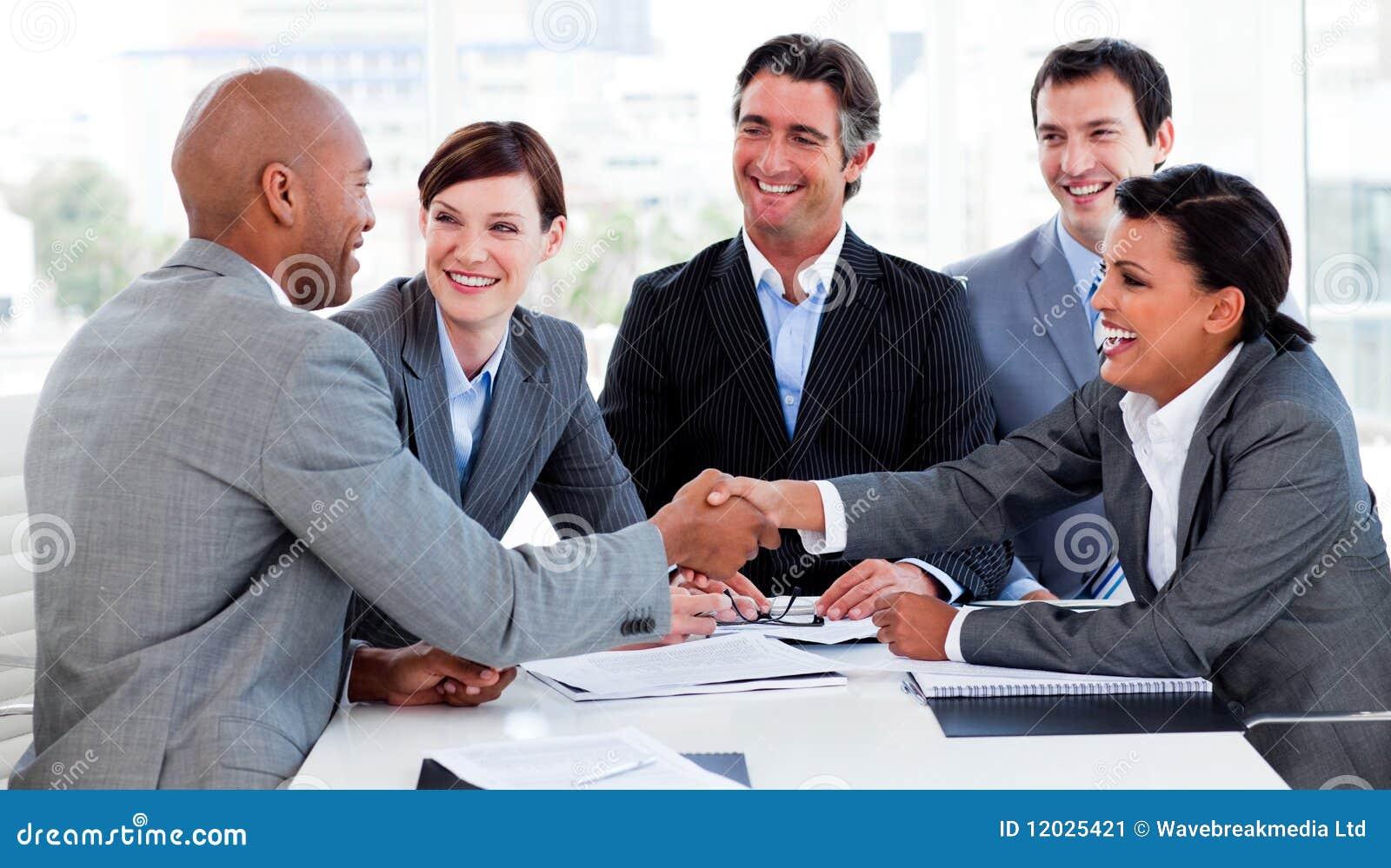 Multi-etnische bedrijfsmensen die elkaar begroeten