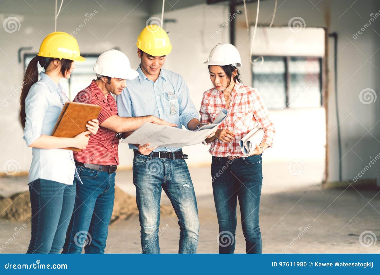 Multi-etnische diverse groep die ingenieurs of partners bij bouwwerf, bij de bouw van de blauwdruk van ` samenwerken s