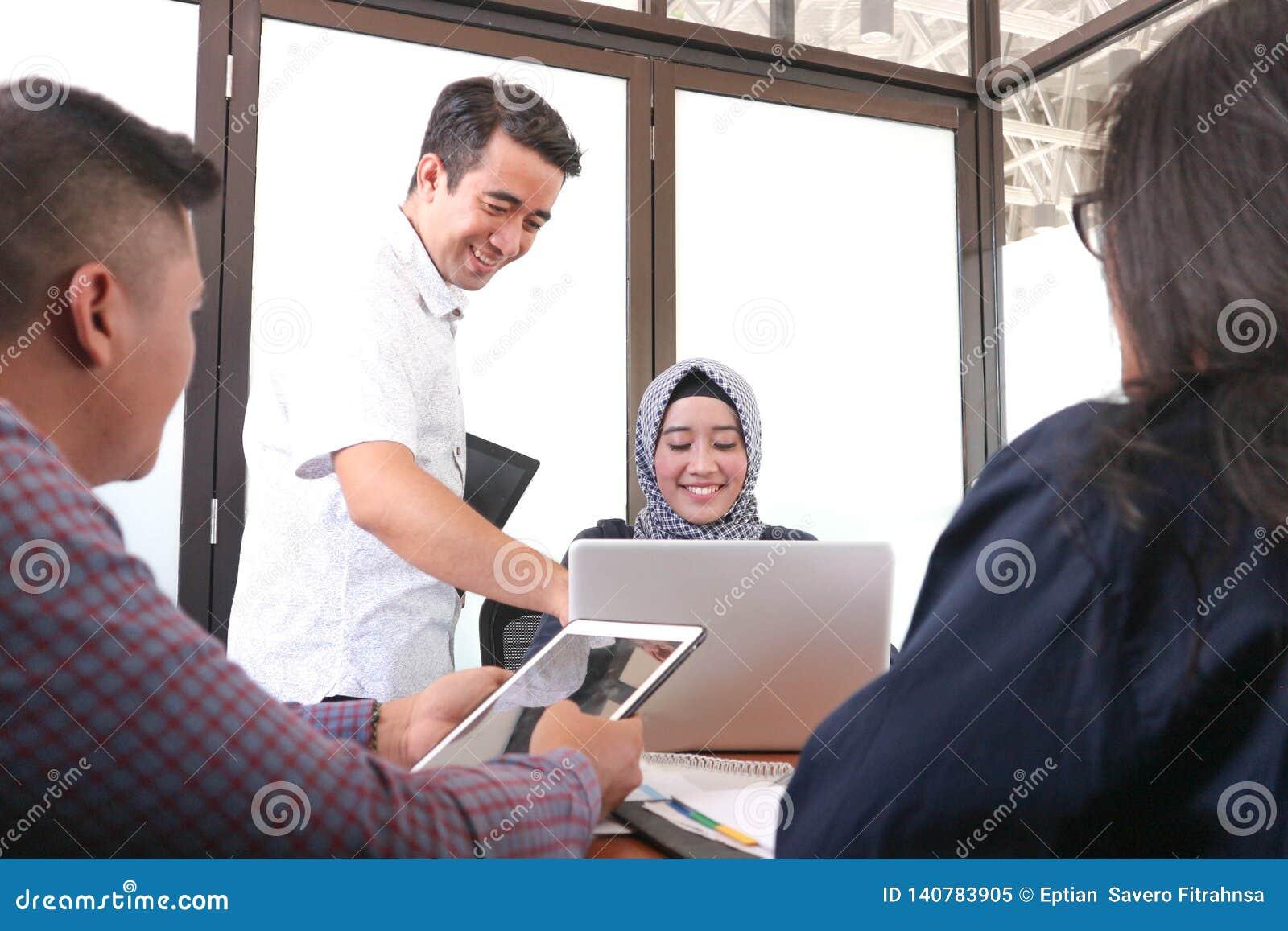 Multi-etnische groep gelukkige bedrijfsmensen die samen met laptop en tablet werken