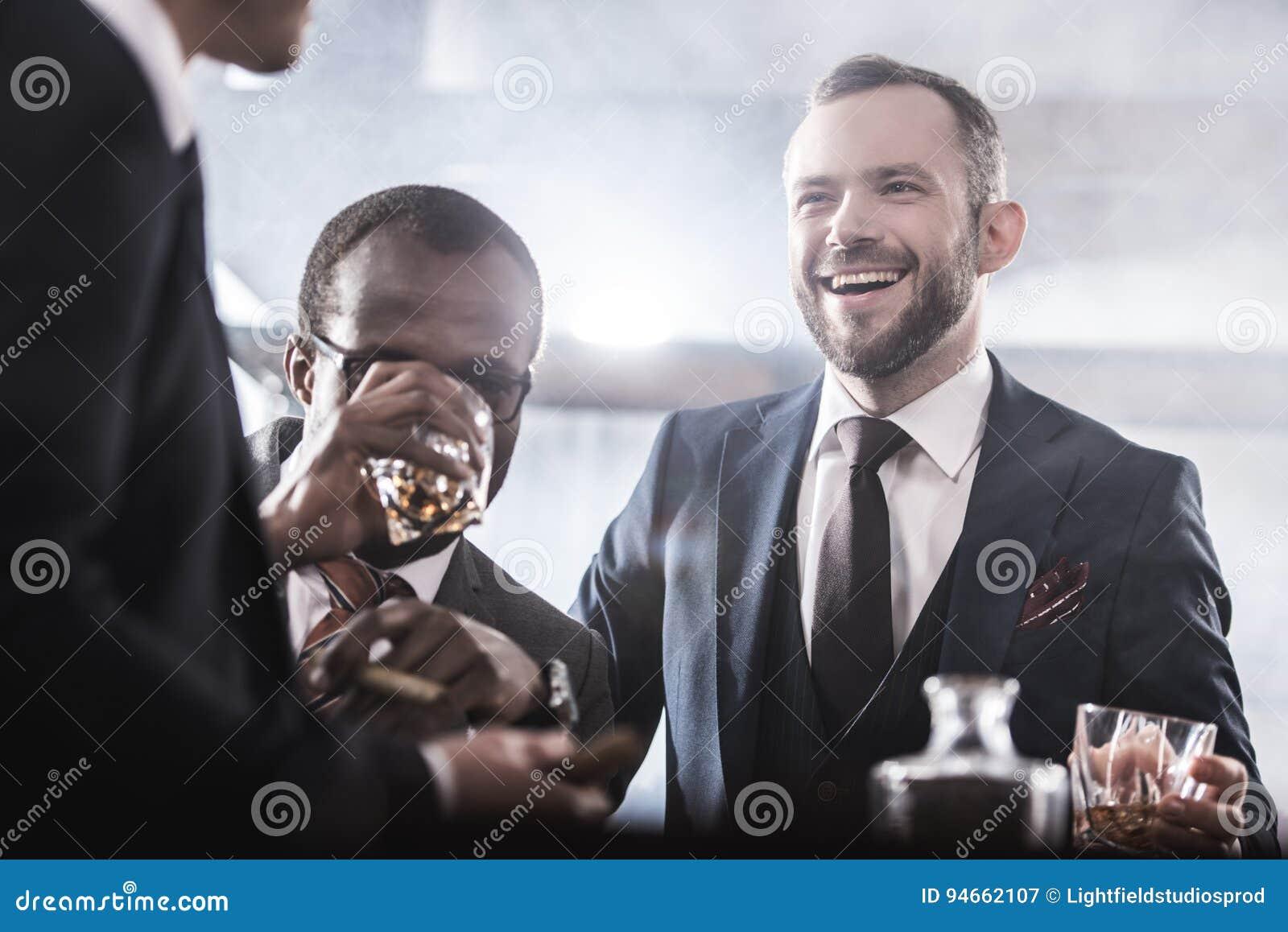 Multi-etnische groep zakenlieden die tijd doorbrengen die samen whisky en het roken drinken