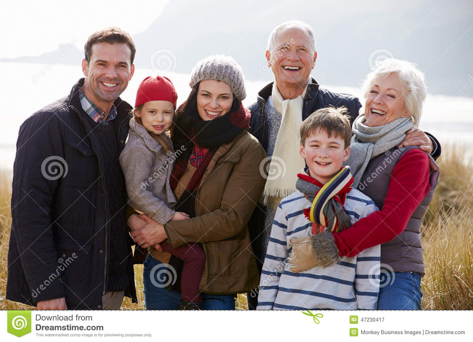 Multi família da geração em dunas de areia na praia do inverno