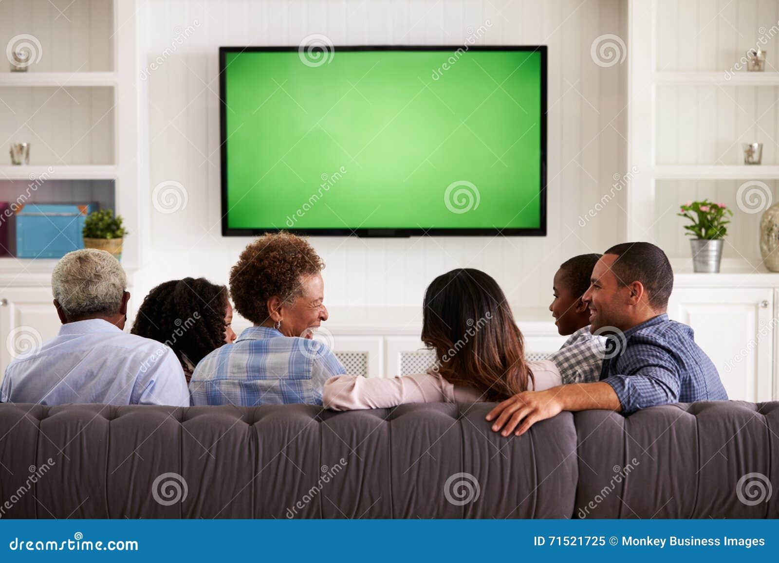 Multi família da geração que olha a tevê e que ri, vista traseira