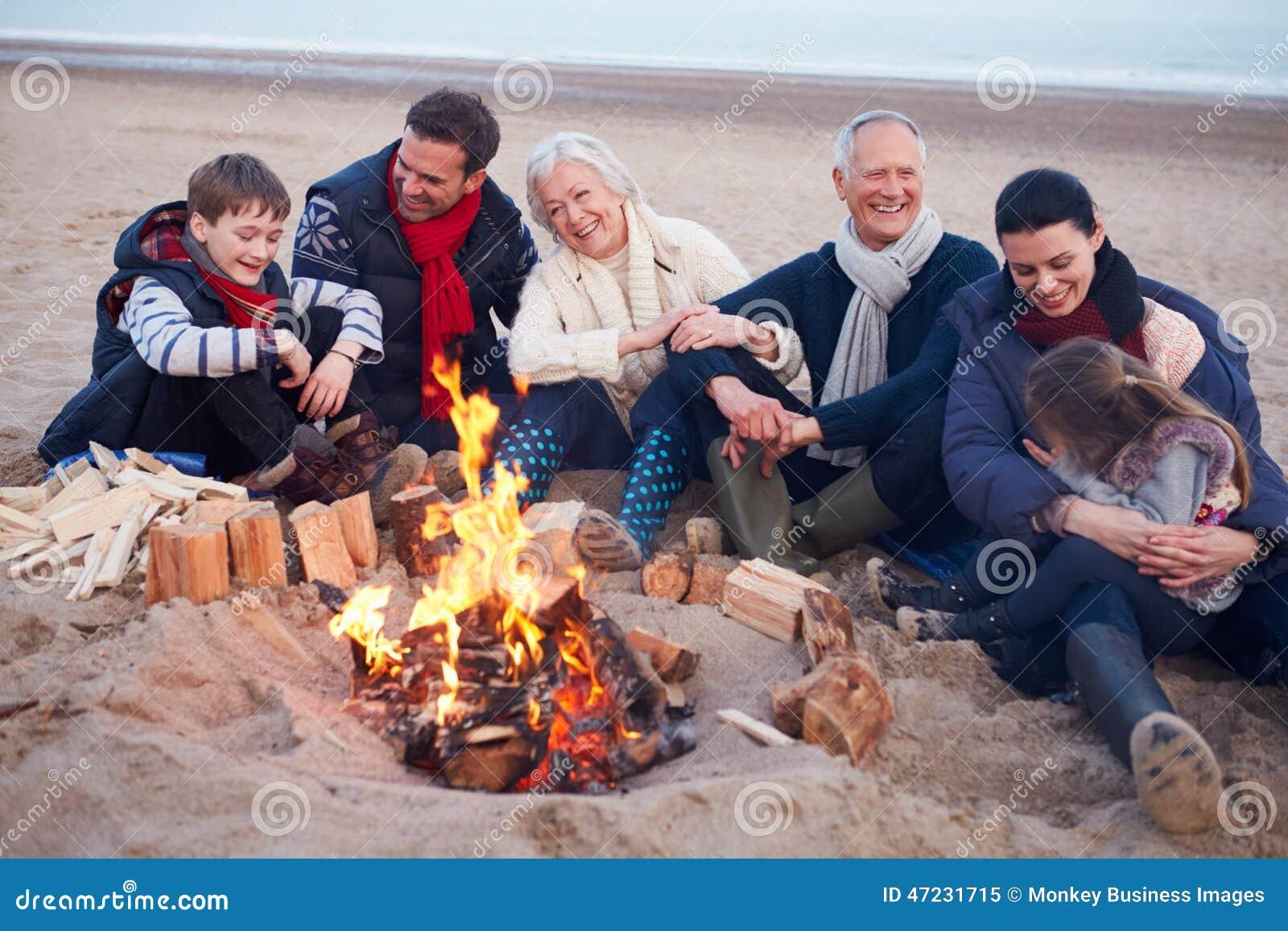 Multi família da geração que senta-se pelo fogo na praia do inverno