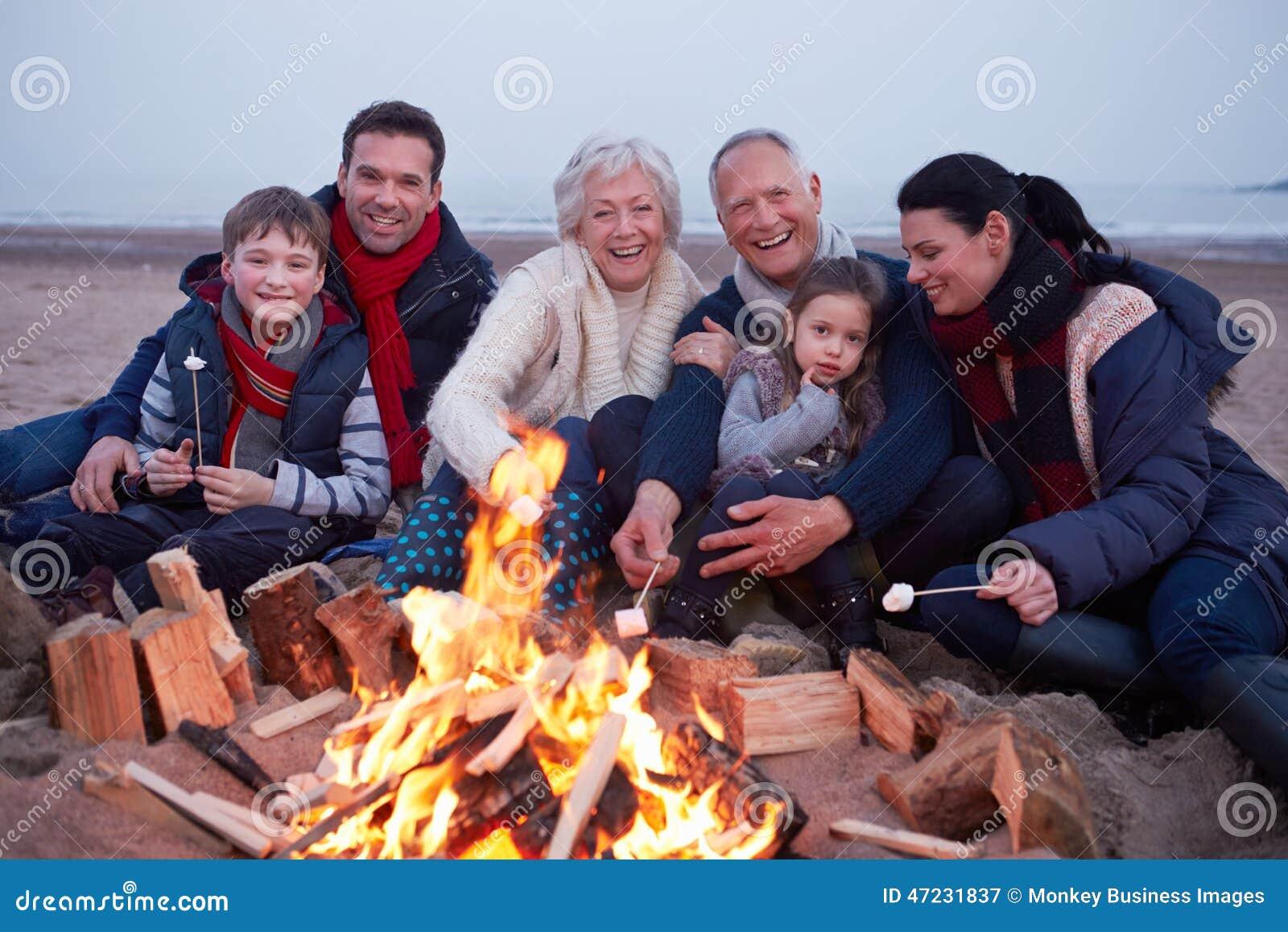 Multi família da geração que tem o assado na praia do inverno
