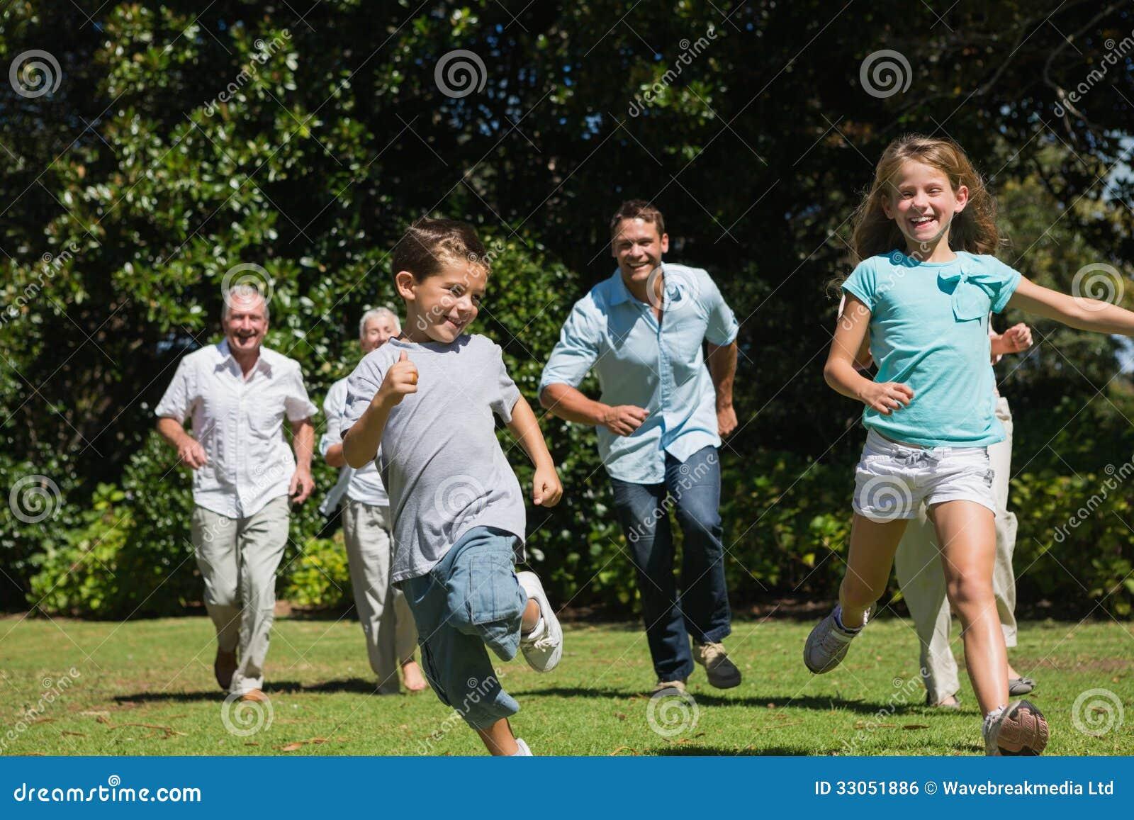 Multi famiglia felice della generazione che corre verso la macchina fotografica