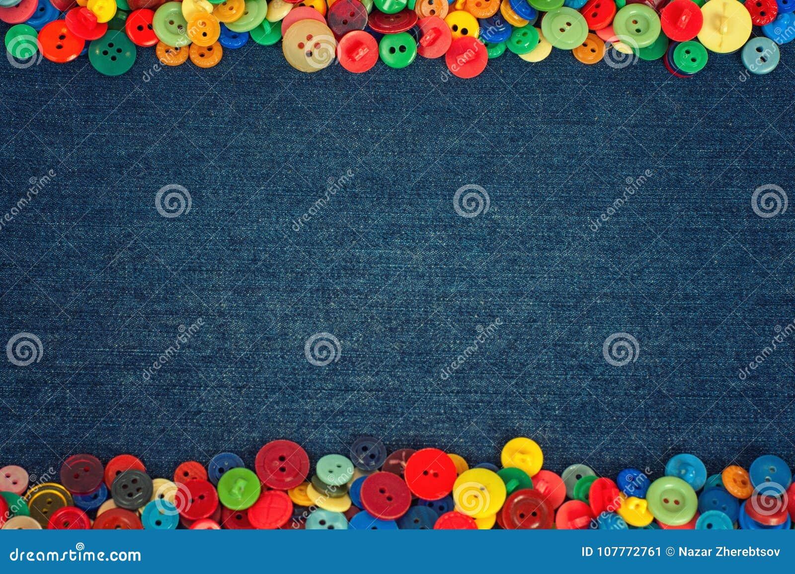 Multi gekleurde knopen aan de kant van een achtergrond van de denimstof