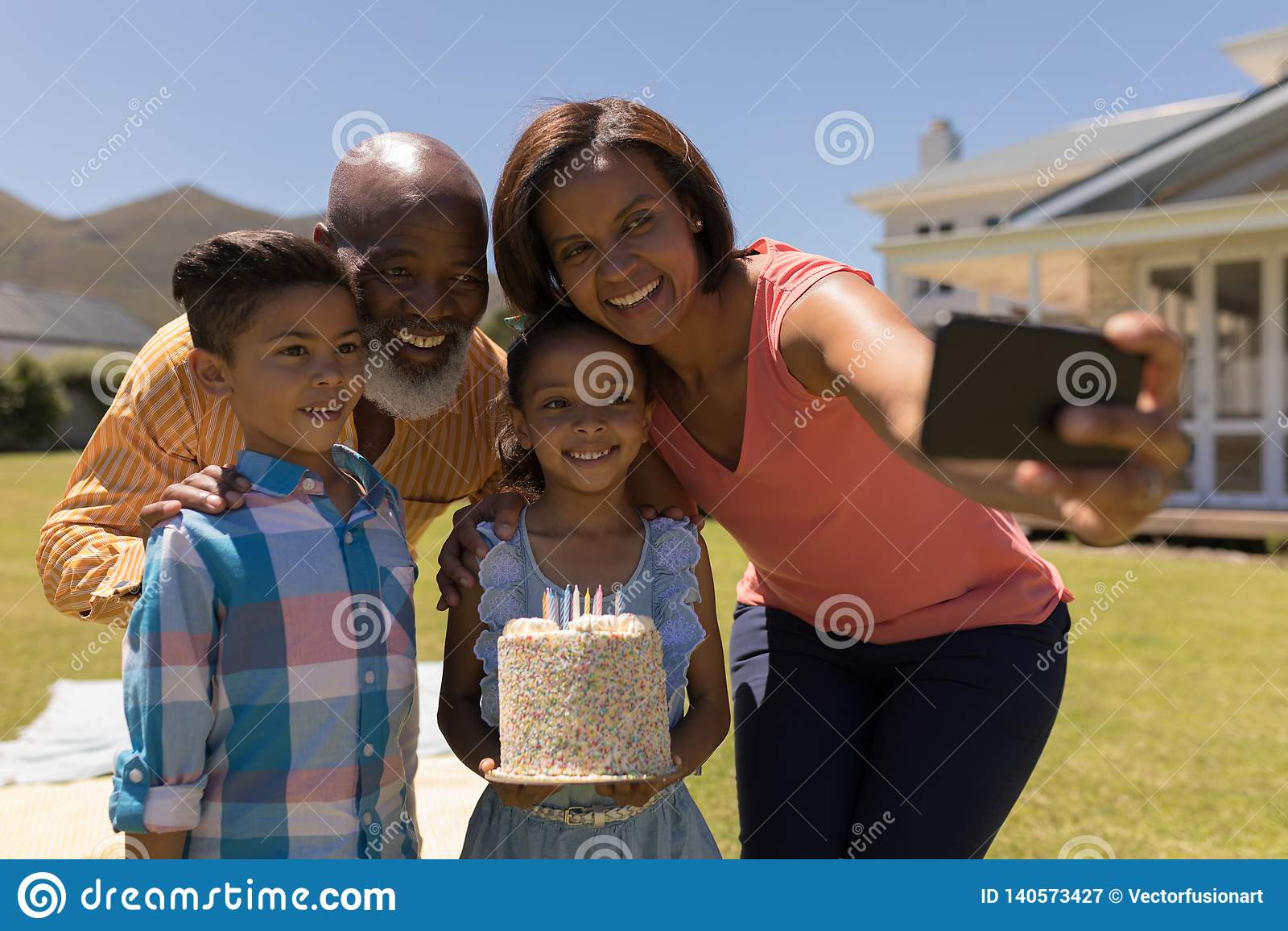 Multi-generation οικογένεια που παίρνει selfie με το κινητό τηλέφωνο γιορτάζοντας τα γενέθλια του grandaughter