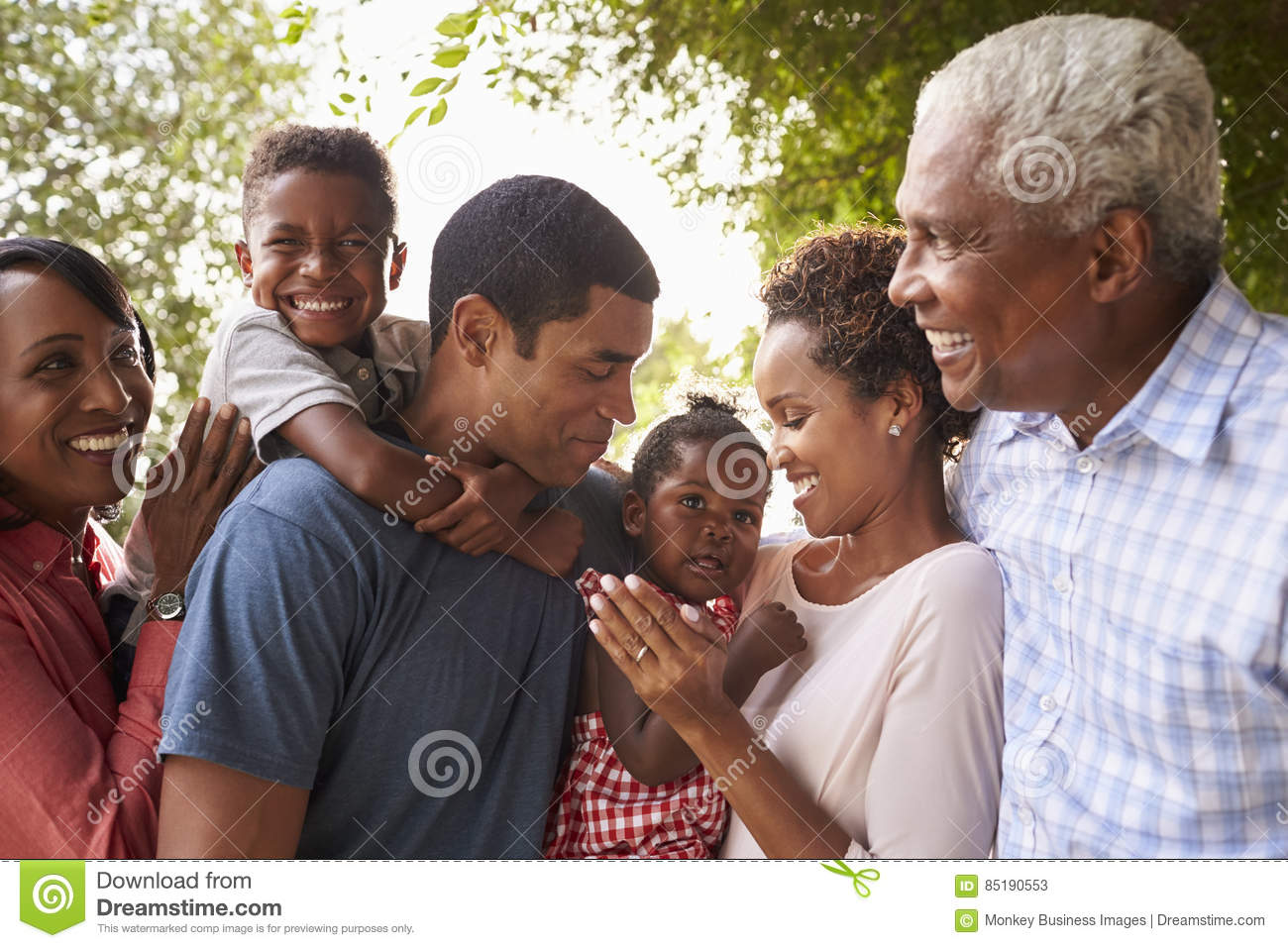 Multi generation black family look at each other in garden