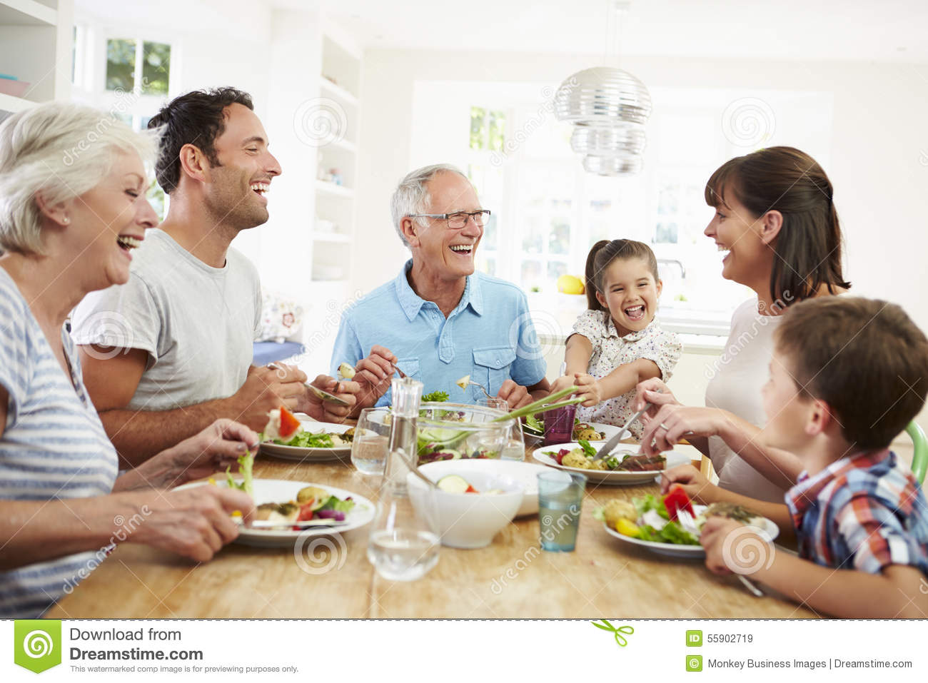 Multi generation family eating meal around kitchen table for Eating table