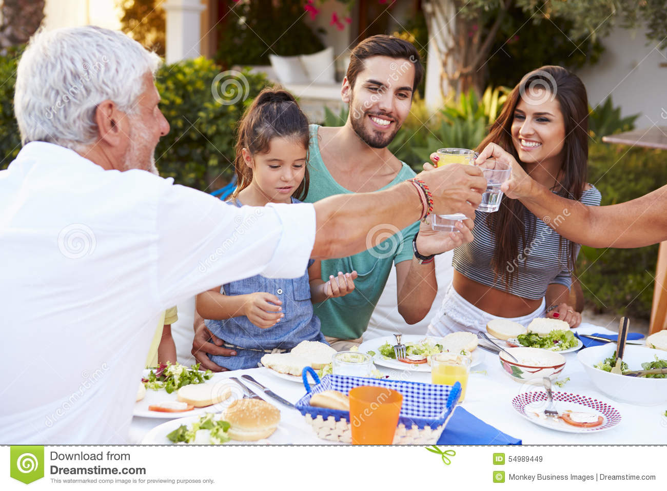 Multi generation family eating meal at outdoors together for Meal outdoors
