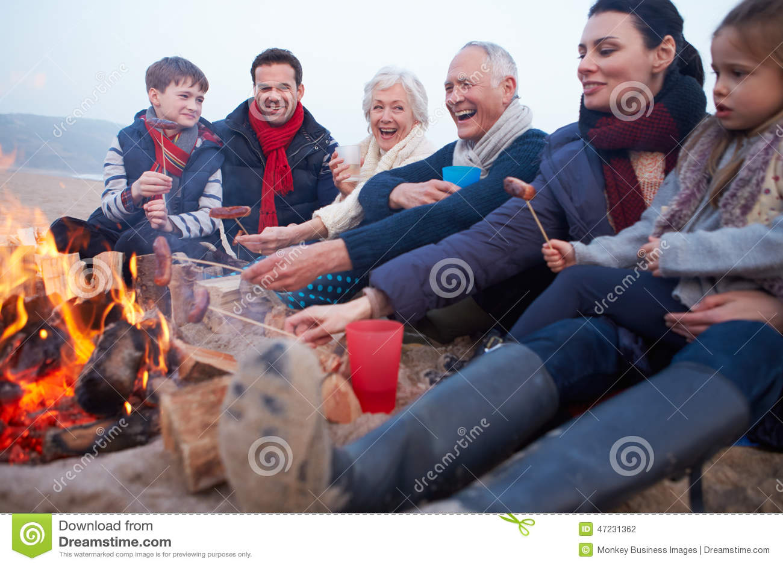 Multi Generation Family Having Barbeque On Winter Beach