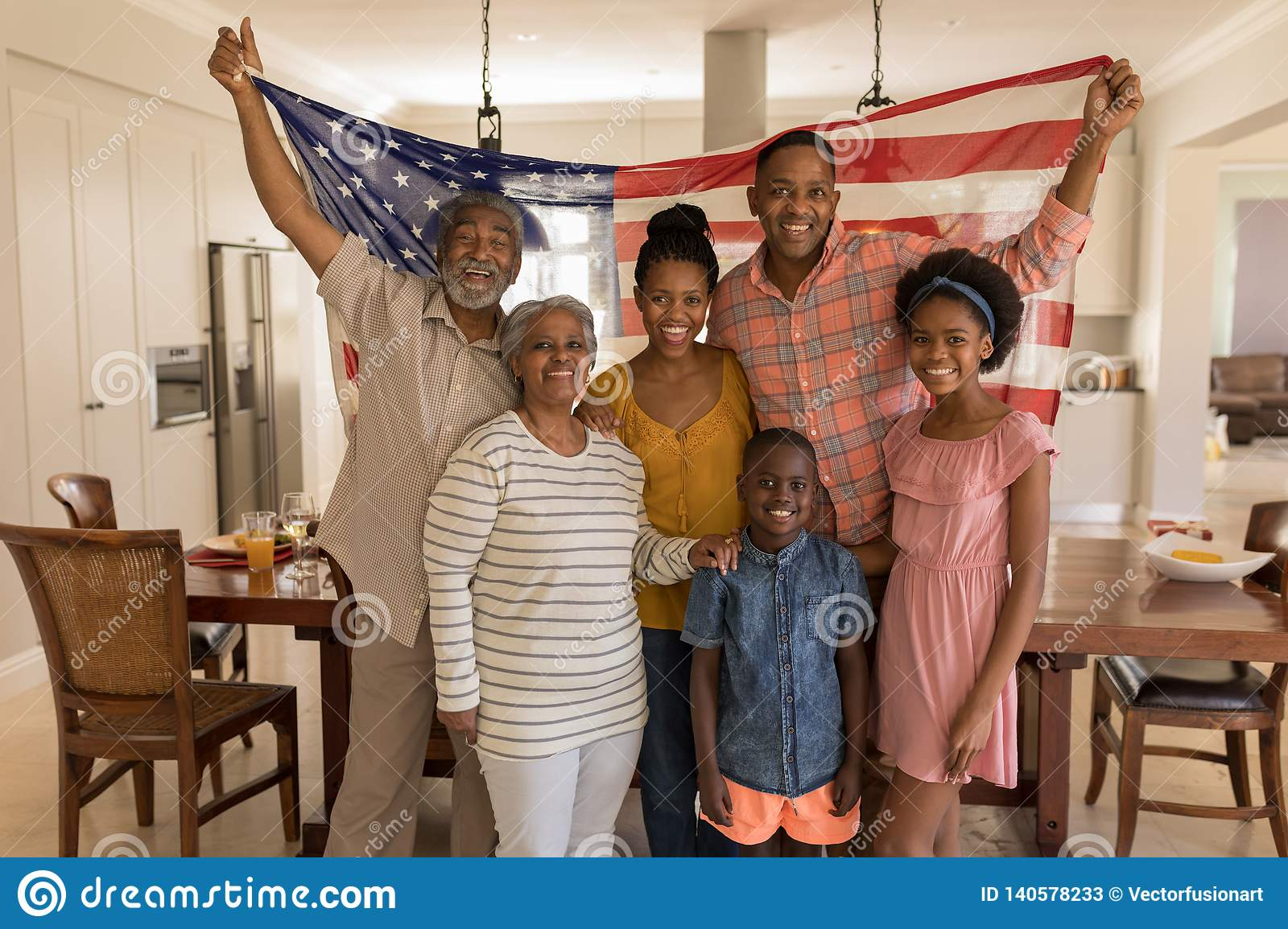 Multi-generation family holding an American flag at home