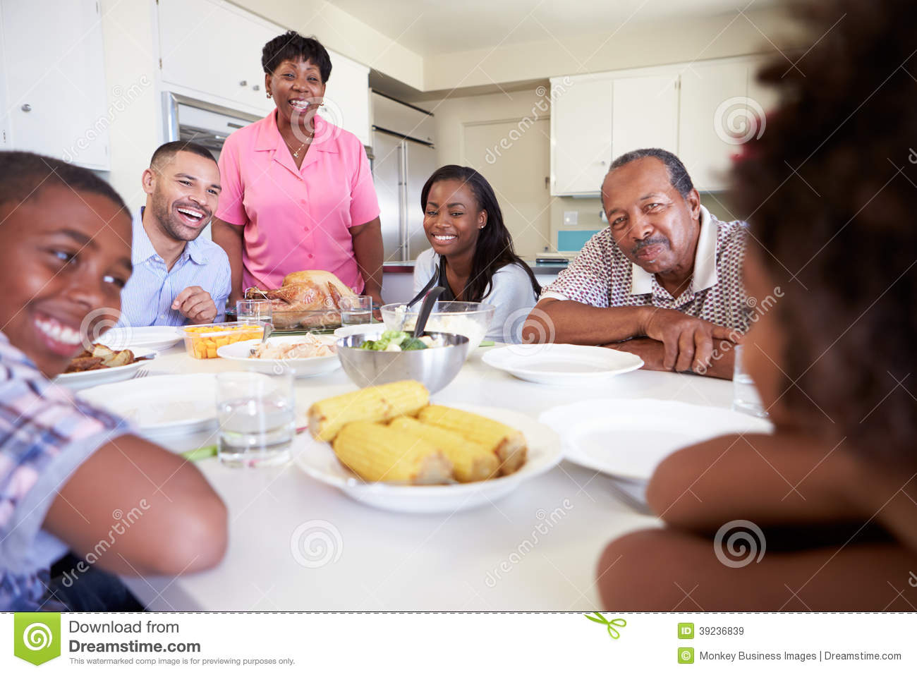 Multi generation family sitting around table eating meal for Eating table