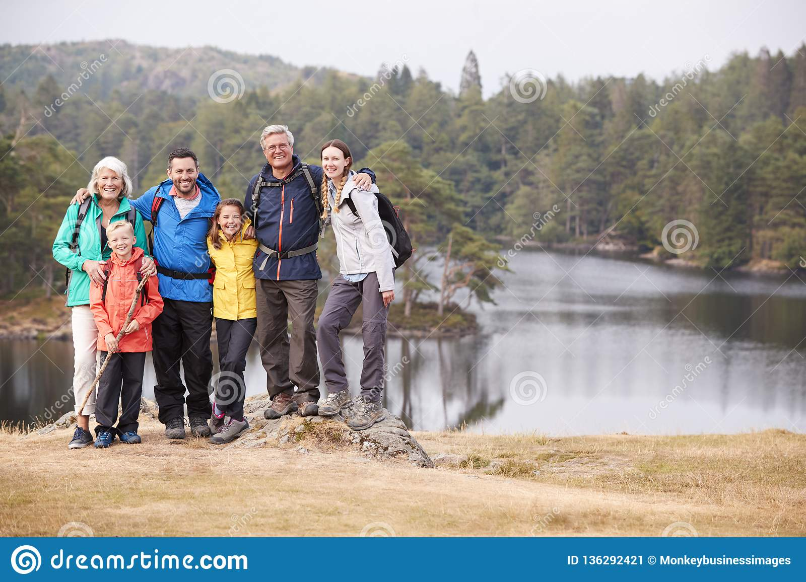 Multi generation family stand embracing by a lake, smiling to camera, front view, Lake District, UK