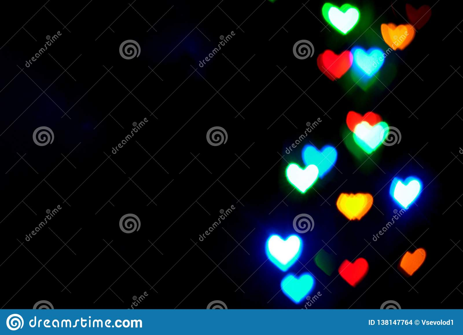 Multi luzes borradas coloridas na forma dos corações na obscuridade