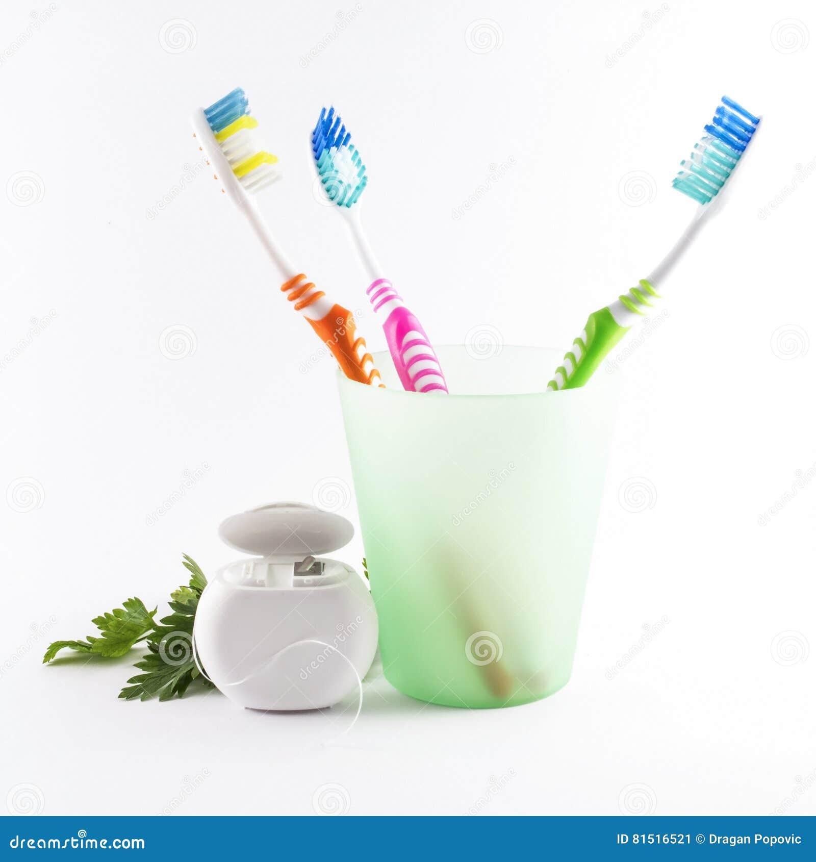 Multicolor зубные щетки и зубоврачебная зубочистка на белой предпосылке