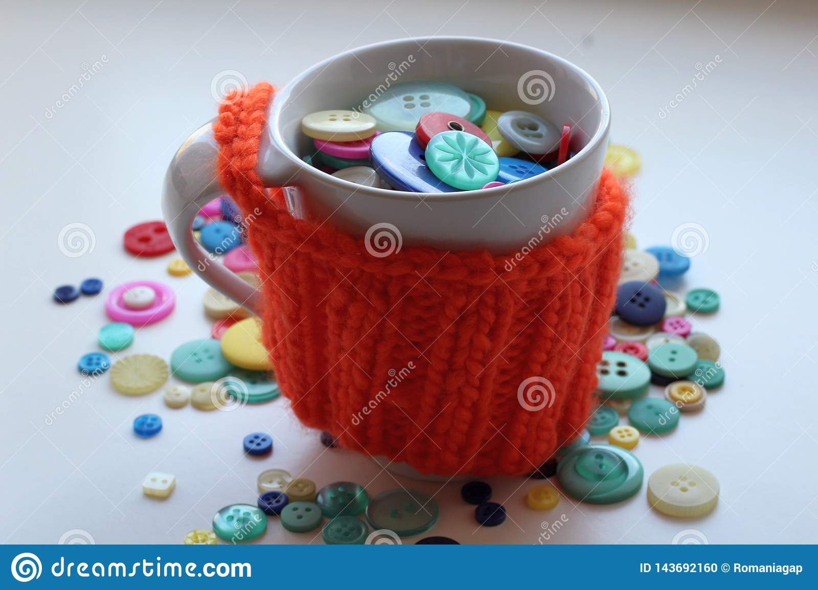 Multicolored buttons in a white cup wrapped in a knitted and warm orange case