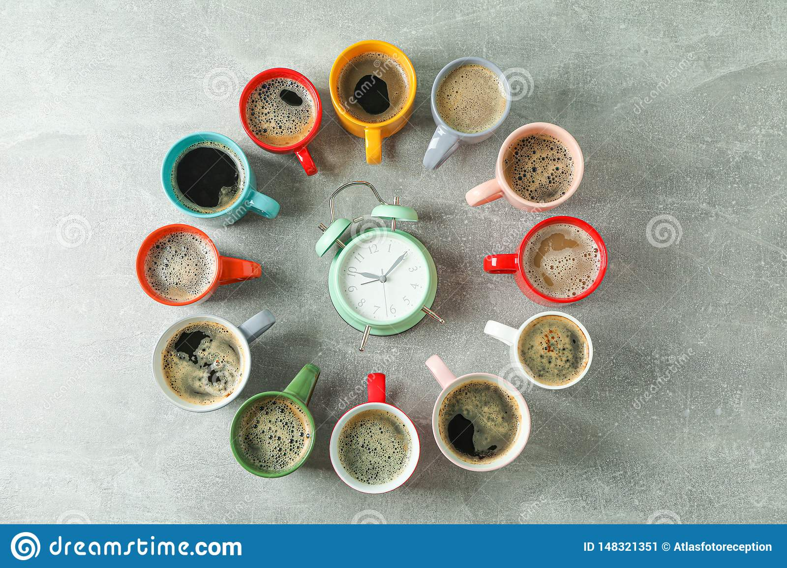 Multicolored cups of coffee circle and alarm clock on grey background, top view
