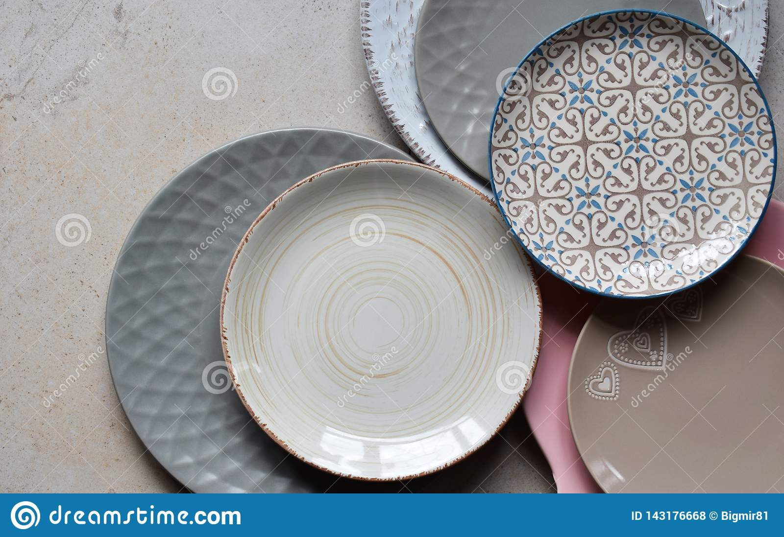 Multicolored empty ceramic plates and bowls on a marble background. Table setting. Shabby chic or retro style. Copy space. Mock up