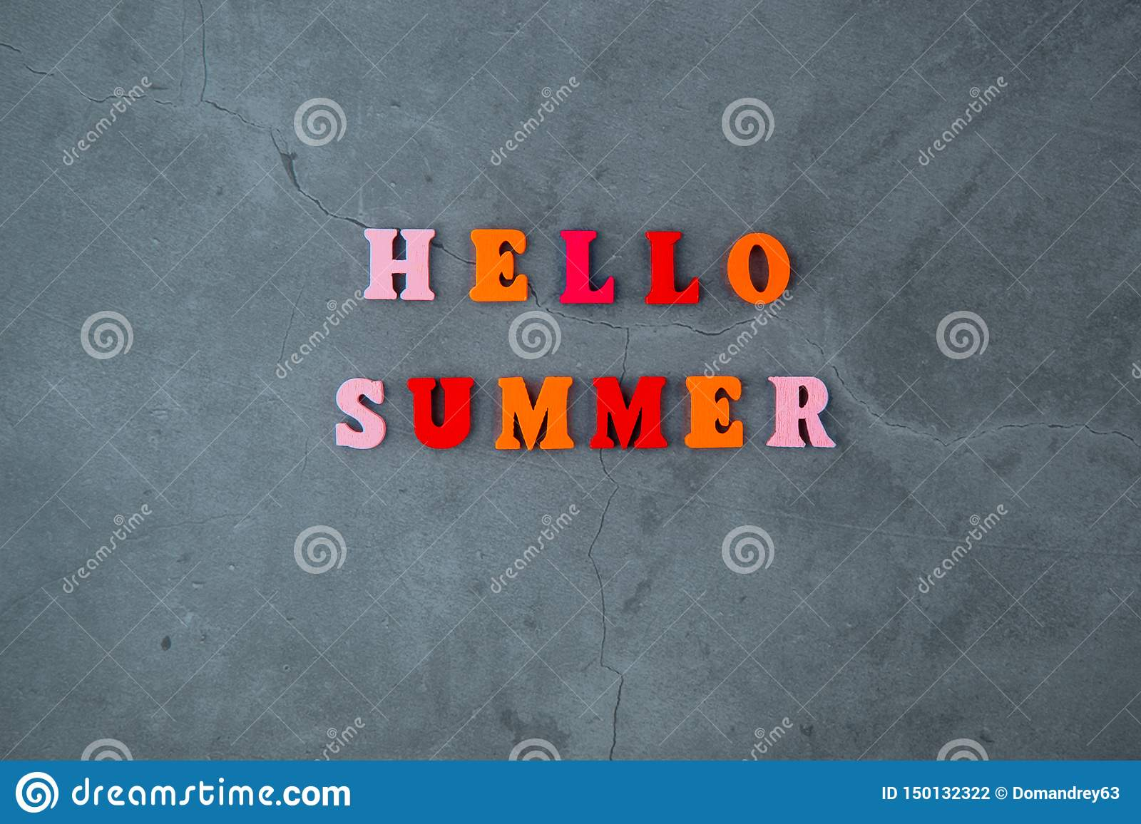 The multicolored hello summer word is made of wooden letters on a grey plastered wall background