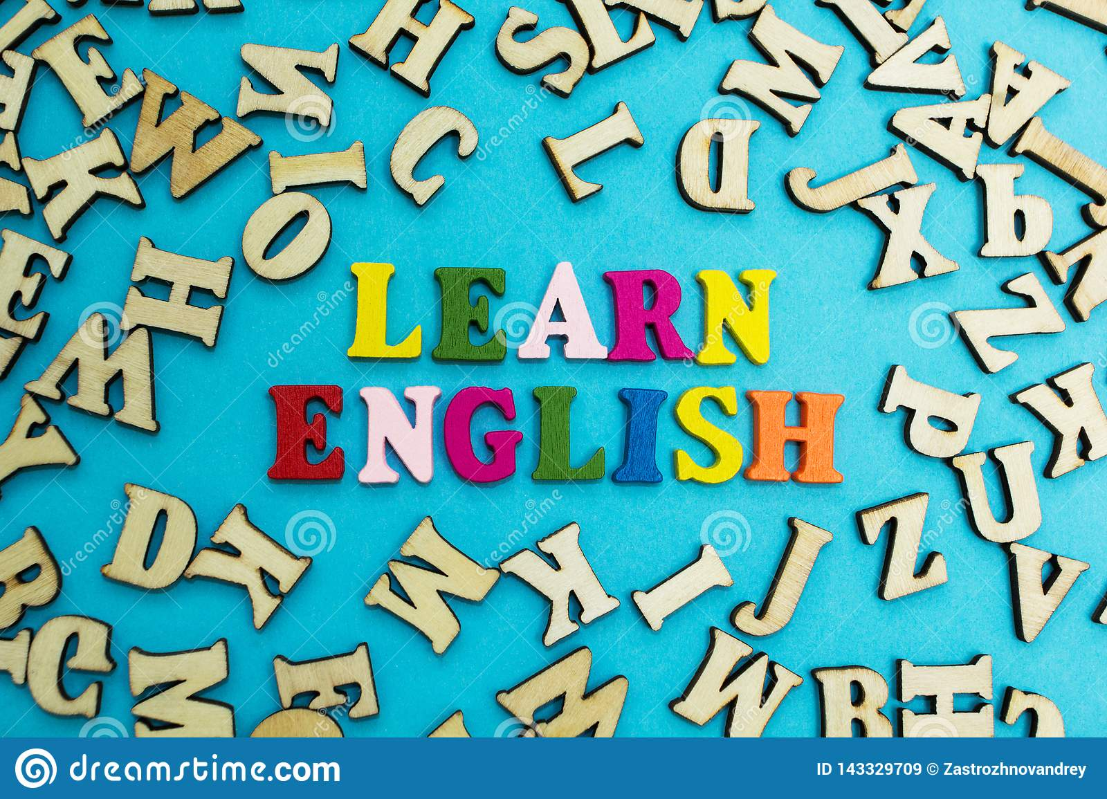 Multicolored inscription `learn English` on a blue background, scattered letters