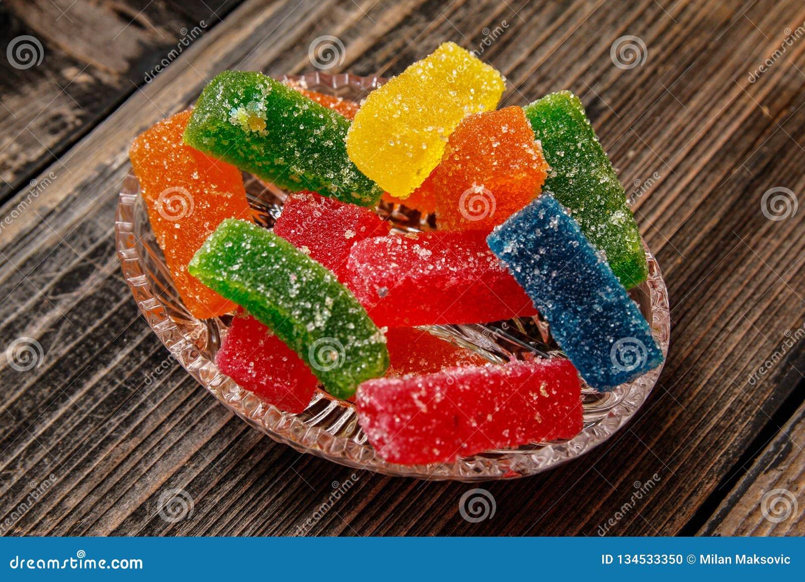 Multicolored kleverig die suikergoed met suiker met een laag wordt bedekt