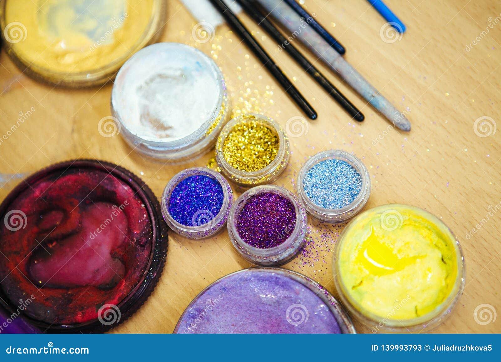 Multicolored lovertjes in transparante kruiken, en make-upborstel Sluit omhoog
