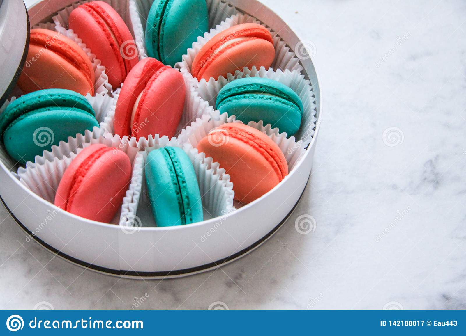 Multi-colored delicious homemade macarons in a round white box on a marble background