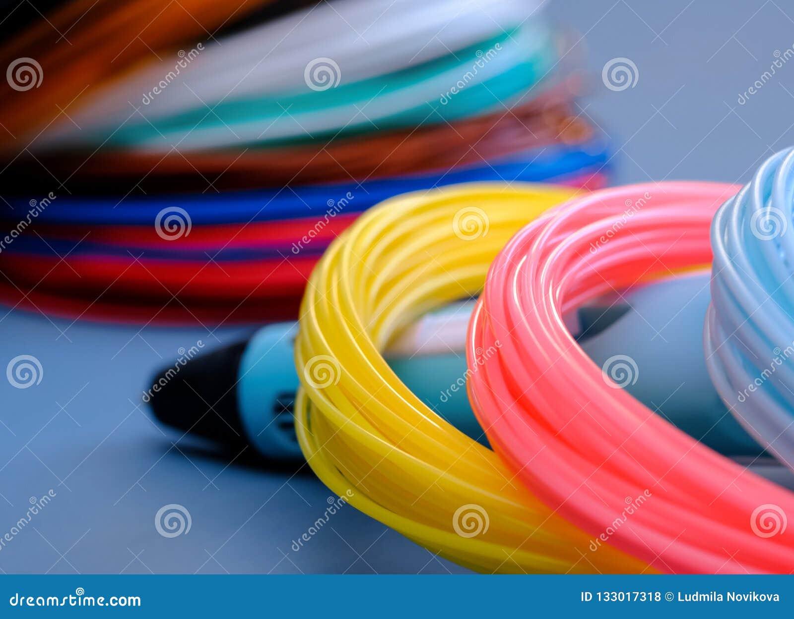Multicolored plastic en 3D pen van ABS/PLN op een blauwe achtergrond
