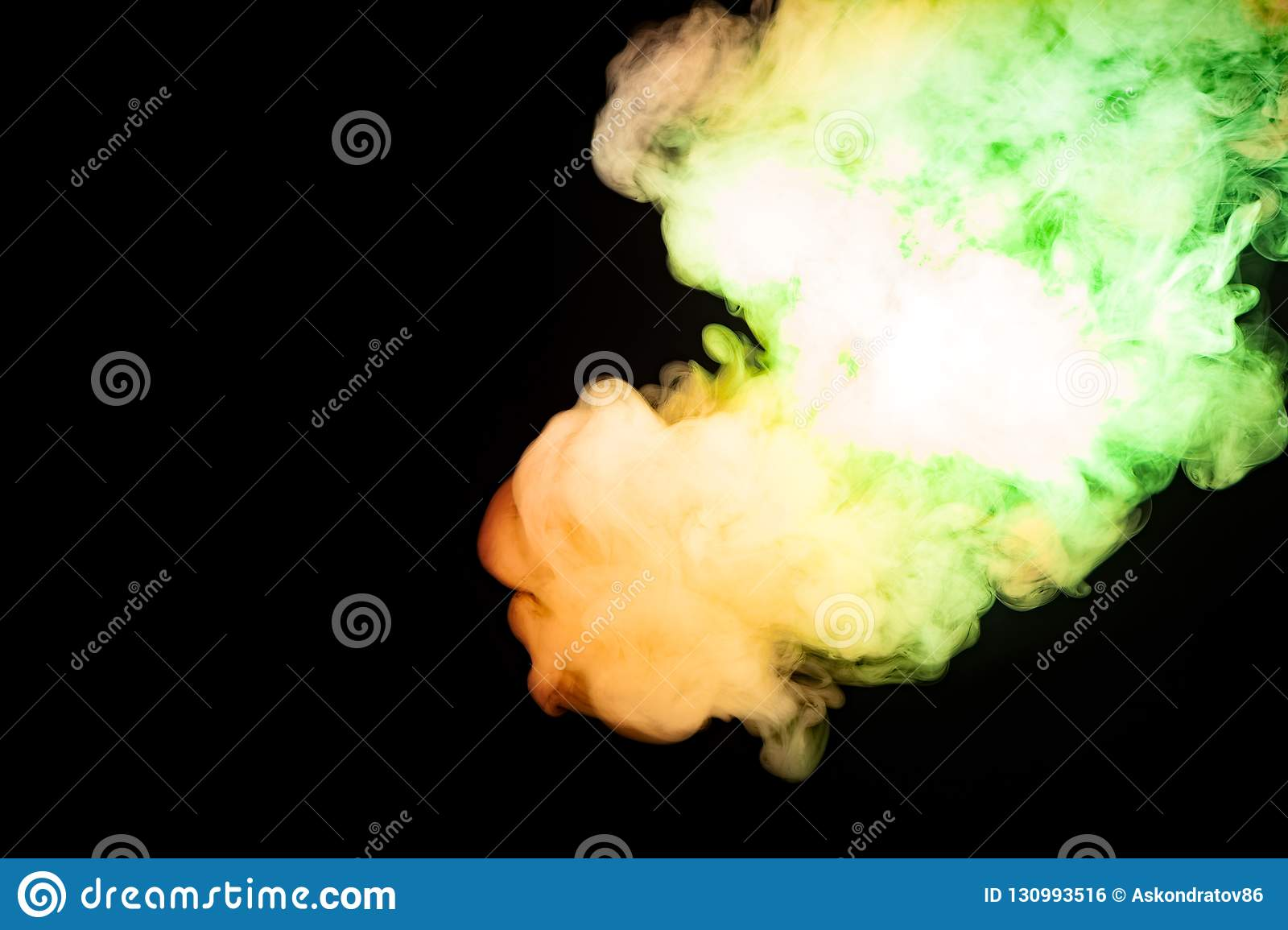 Multicolored smoke of red yellow and green colors from a vap scattering on a black isolated background