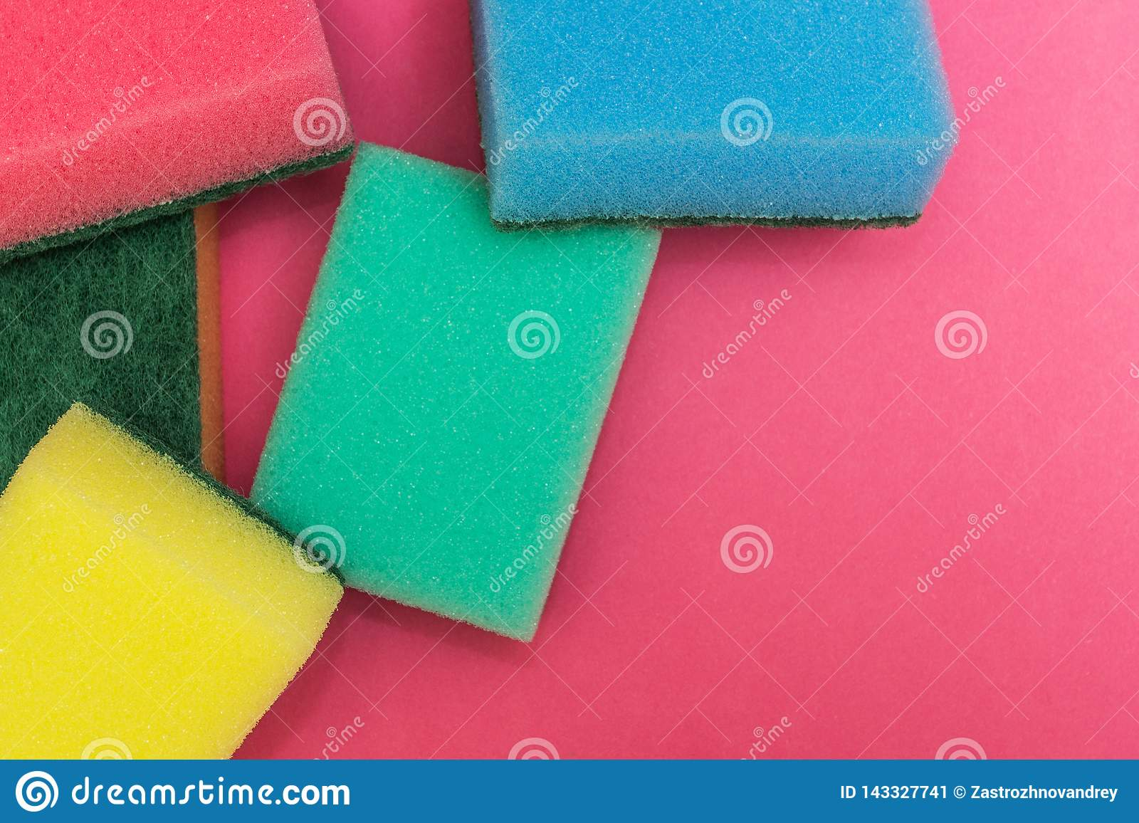 Multicolored sponges on a pink background