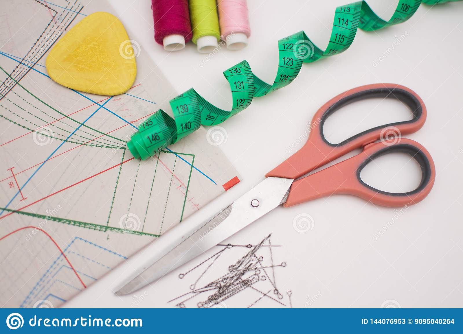 Multicolored thread coils and measuring tape on white background.