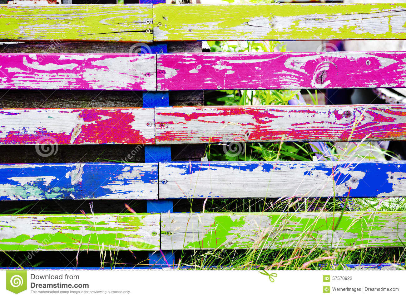 Multicolored wooden fence with grass stock photo image