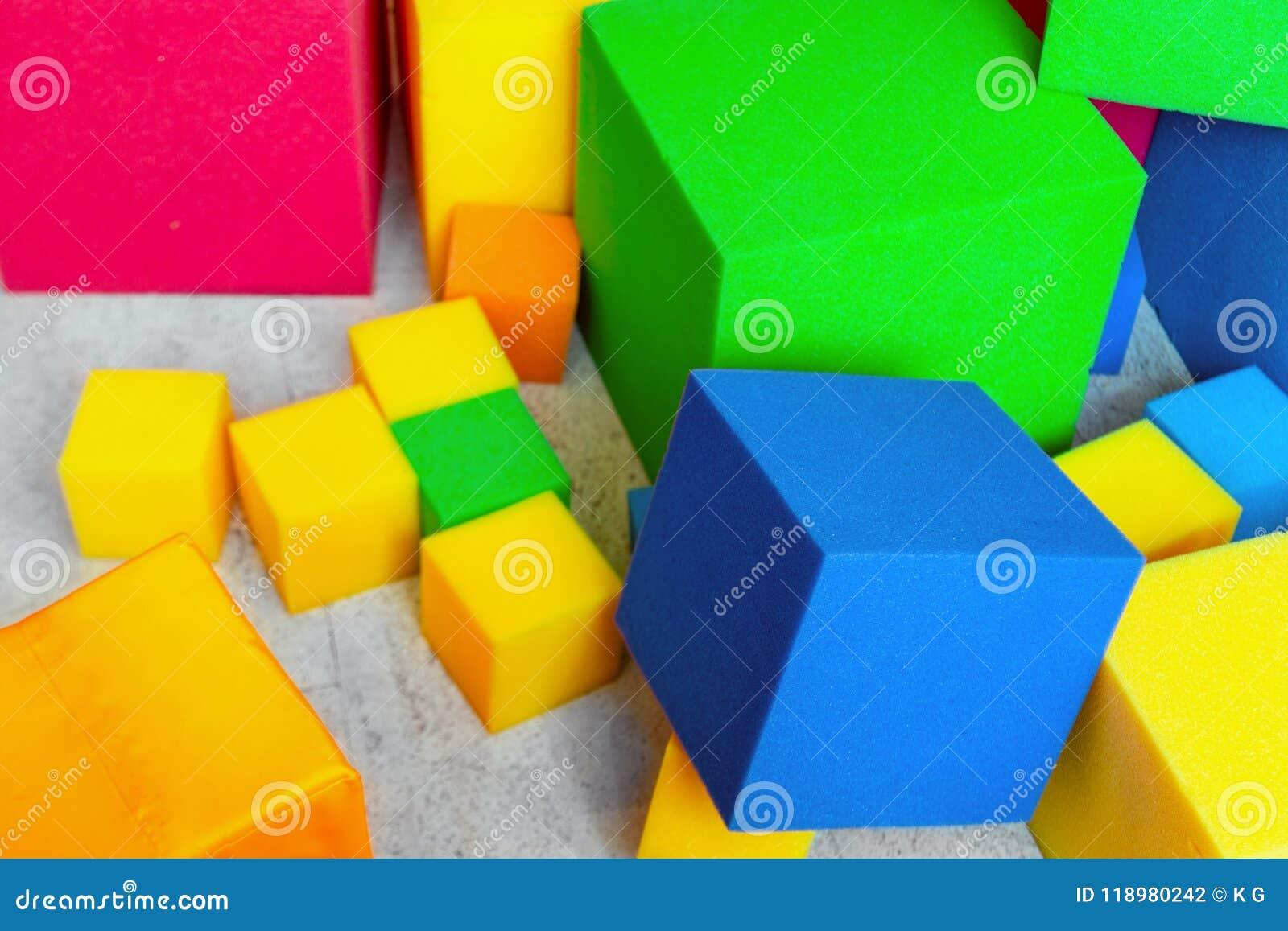 Multicolored zachte schuimkubussen bij kinderenspeelplaats Helder kleurrijk speelgoed Het vermaak en de decoratie van de jonge ge