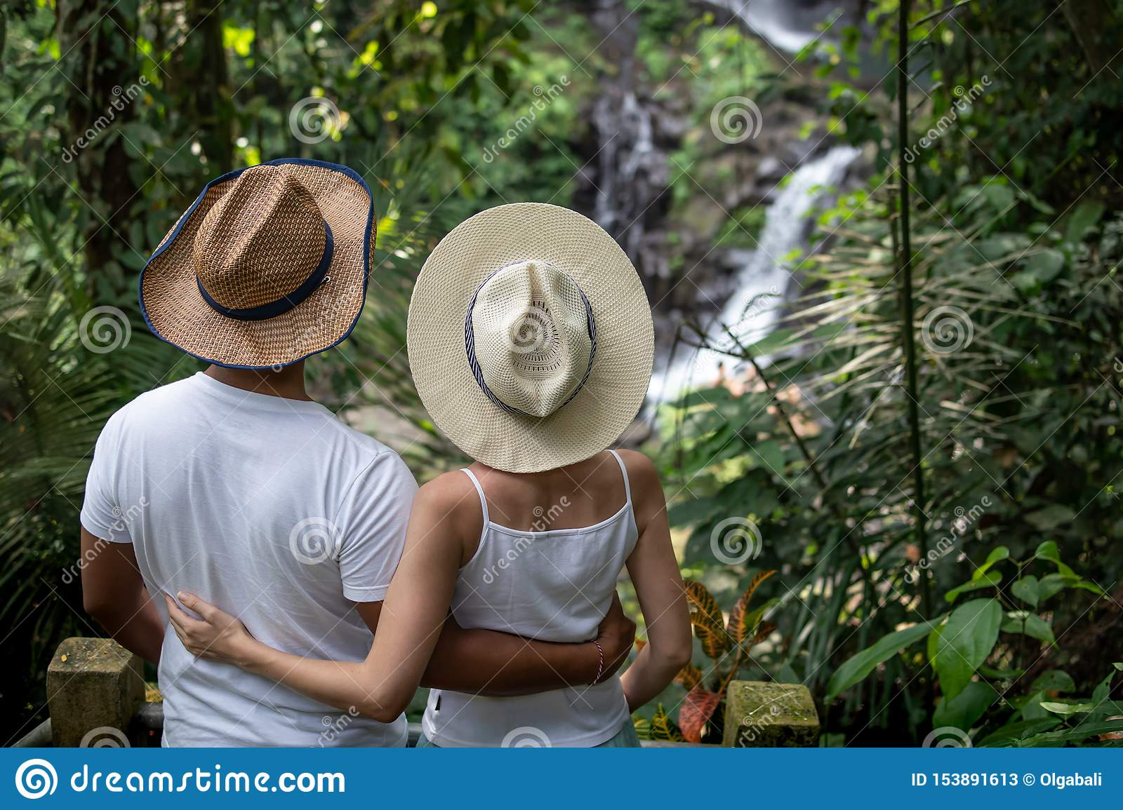 Multicultural couple enjoying waterfall scenery in tropical rainforest. Young mixed race couple on vacation in Asia. Pengibul