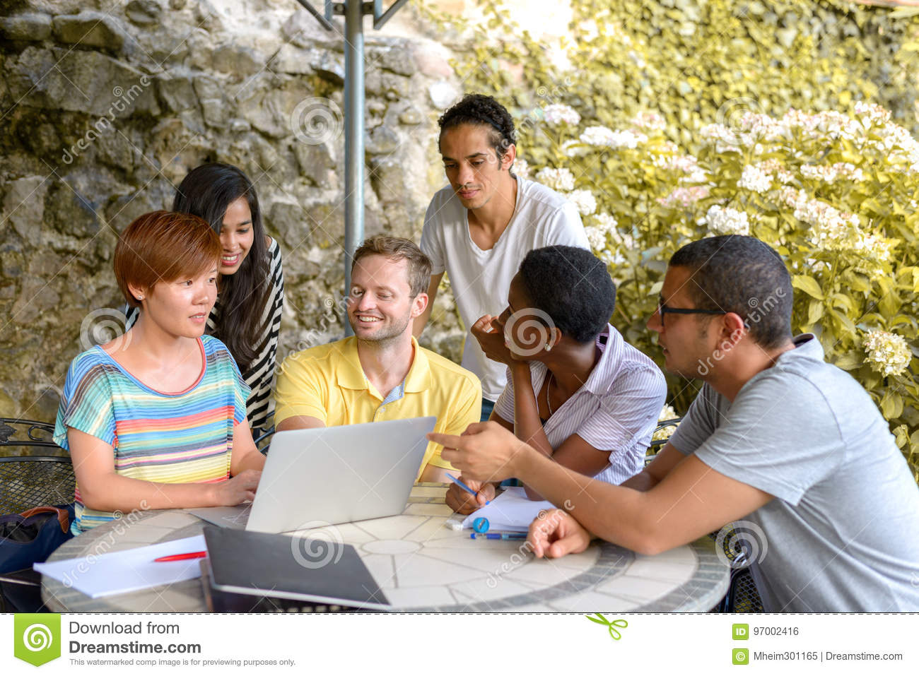Multicultural group of people discussing by laptop