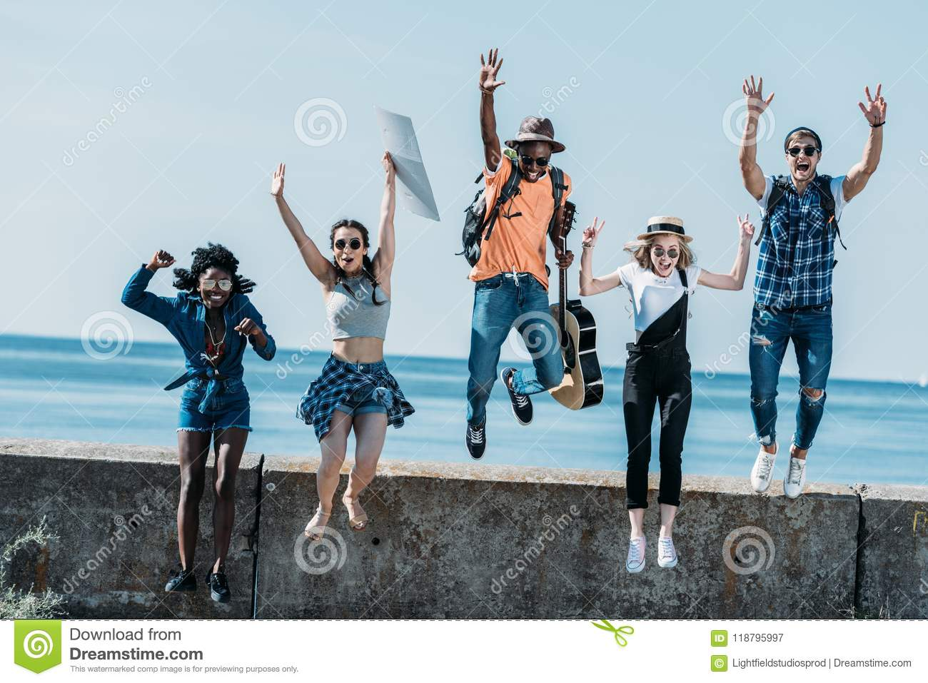 multicultural group of young friends jumping of