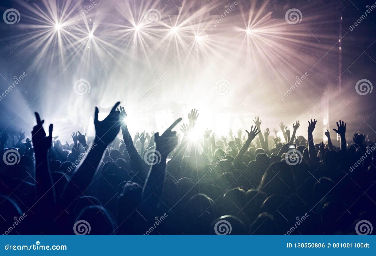 Multidão do concerto, mãos na luz do arco-íris