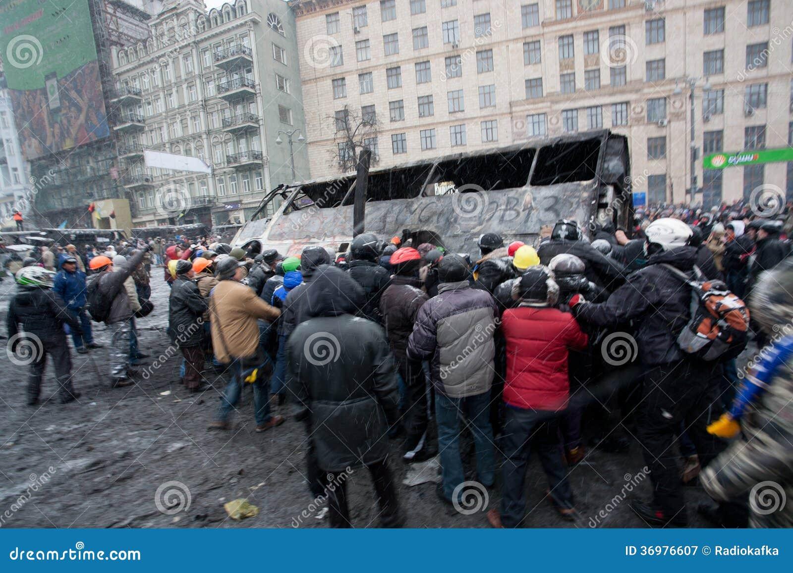 A multidão irritada na rua de ocupação virada queima o ônibus no demostration durante o protesto antigovernamental Euromaidan