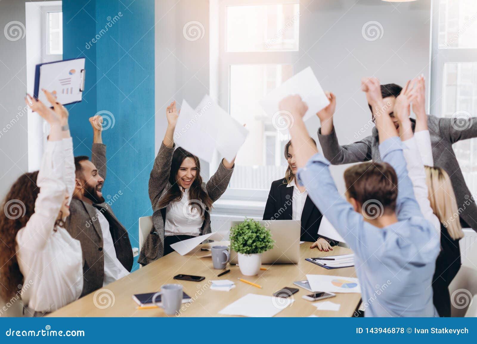 Η διαφορετική ευτυχής ομάδα Multiethnic γιορτάζει την επιτυχία προγράμματος ρίχνει το έγγραφο επάνω από κοινού Εταιρική κοινότητα